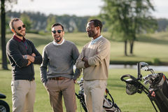 一起花费时间的不同种族的高尔夫球运动员在高尔夫球场 免版税库存图片