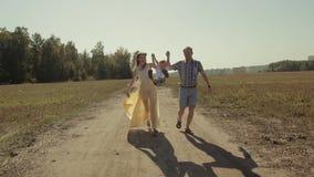 一起花费他们的时间的美丽的年轻家庭在领域 他们跑,笑,拿着每othe是手 股票视频