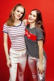 一起获得两个最好的朋友的十几岁的女孩乐趣,摆在情感在红色背景, besties愉快微笑,生活方式 免版税库存图片