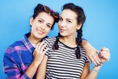 一起获得最好的朋友少年学校的女孩乐趣,摆在情感在蓝色背景, besties愉快微笑 库存照片