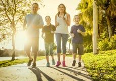 一起行使和跑步在公园的家庭 免版税库存图片