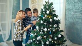 一起装饰圣诞树的愉快的家庭 父亲、母亲和儿子 股票视频