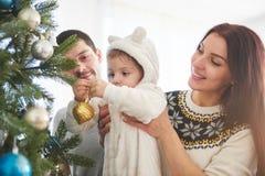 一起装饰圣诞树的愉快的家庭 父亲、母亲和女儿 逗人喜爱的子项 库存图片