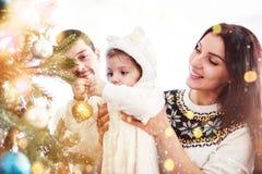 一起装饰圣诞树的愉快的家庭 父亲、母亲和女儿 逗人喜爱的子项 免版税库存图片
