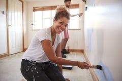 一起装饰新的家庭绘的墙壁的夫妇画象室 库存照片