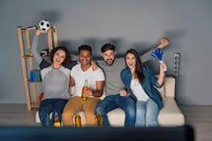 一起观看体育的小组朋友 免版税库存图片