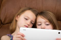 一起观看片剂的两个女孩 图库摄影