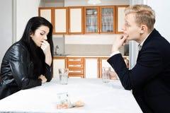 一起解决金融危机的夫妇在桌上在厨房里 免版税库存图片