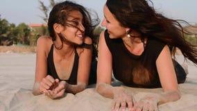 一起说谎在沙滩,谈话和笑的母亲和青少年的女儿 影视素材