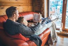 一起说谎在舒适沙发的父亲和儿子看书在温暖的乡间别墅里 对孩子概念性图象的读书 图库摄影