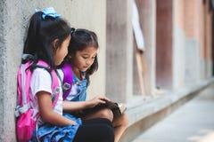 一起读书的两个逗人喜爱的亚裔学生女孩在充满乐趣和幸福的学校 免版税库存照片