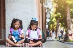 一起读书的两个逗人喜爱的亚裔学生女孩在充满乐趣和幸福的学校 免版税库存图片
