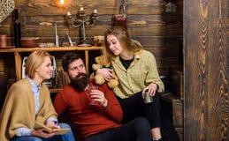 一起读在长沙发的书痴家庭  父母和十几岁的女儿消费圣诞节在乡下 博若莱红葡萄酒 库存图片