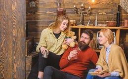 一起读在长沙发的书痴家庭  父母和十几岁的女儿消费圣诞节在乡下 有胡子 免版税库存照片