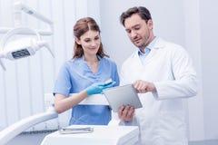 一起谈论工作和使用片剂的年轻牙医在牙齿诊所 免版税图库摄影