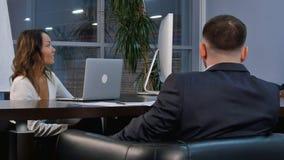 一起谈话小组成功的买卖人,当工作在一张桌附近在办公室会议室里时 库存图片