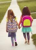 一起走到学校的小女孩 免版税库存图片
