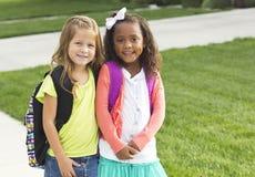 一起走到学校的逗人喜爱的小女孩 免版税图库摄影
