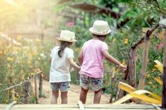 一起走后面观点的两个的小女孩握手和 免版税库存图片