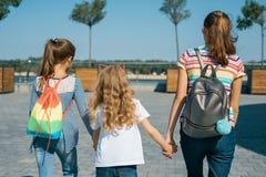 一起走在一个晴朗的夏日,从后面的看法的三个女孩孩子室外画象  免版税库存照片