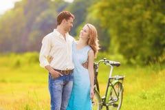 一起走在公园的白种人夫妇户外与自行车 免版税库存图片
