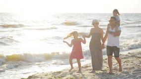 一起走在海附近的愉快的微笑的家庭在晴朗的夏日期间 可爱的加上花费时间的两个孩子  股票视频