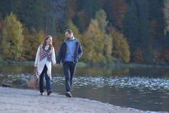 一起走在海滩和握手的年轻夫妇 免版税库存照片