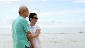 一起走在海滩的亚洲资深夫妇由海 库存图片