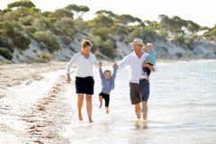 一起走在海滩的年轻愉快的美丽的家庭享受暑假 图库摄影
