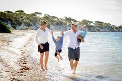 一起走在海滩的年轻愉快的美丽的家庭享受暑假 免版税库存照片