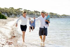 一起走在海滩的年轻愉快的美丽的家庭享受暑假 免版税图库摄影