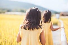 一起走在竹走道的后面观点的两个小女孩 免版税图库摄影