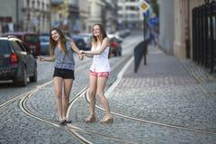 一起走在街道上的路面的滑稽的十几岁的女孩 库存图片