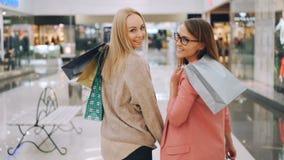 一起走在购物中心的愉快的年轻女人朋友的慢动作拿着然后转向照相机的明亮的袋子 股票录像