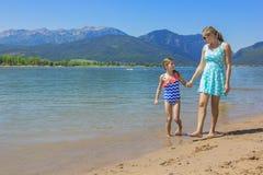 一起走在风景湖的母亲和女儿 免版税库存图片