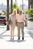一起走沿街道的高级夫妇 库存照片
