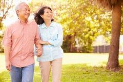 一起走通过公园的资深亚洲夫妇 免版税库存图片