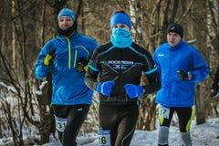 一起跑在一个多雪的公园的小组年轻男性运动员在12月 免版税图库摄影
