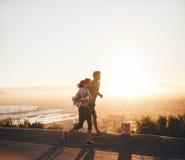 一起跑在山坡路的年轻夫妇 免版税图库摄影