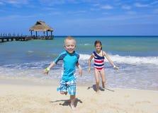 一起跑在海滩的孩子 免版税图库摄影