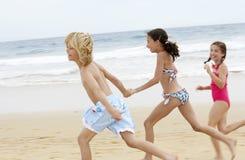一起跑在海滩的快乐的矮小的朋友 库存照片