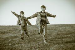 一起跑在草甸,乌贼属的两个男孩被定调子 库存照片