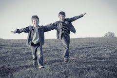 一起跑在草甸,乌贼属的两个男孩被定调子 免版税库存照片