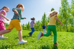 一起跑在绿色公园的许多孩子 免版税库存照片