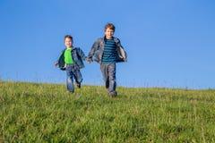 一起跑在绿色草甸的两个男孩 免版税图库摄影