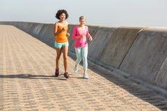 一起跑步两名微笑的运动的妇女 免版税库存图片