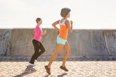 一起跑步两名运动的妇女 免版税图库摄影