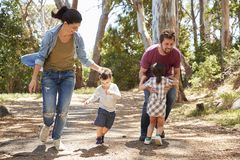 一起跑沿道路的家庭通过森林 库存图片