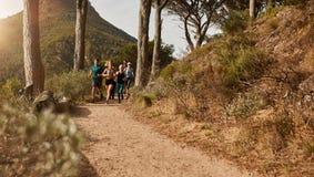 一起跑通过在山坡的足迹的运动员 免版税库存图片