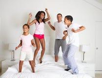 一起跳在床上的家庭 免版税库存图片